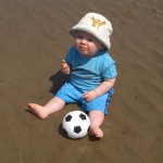 Ben sat on the wet sand with his ball